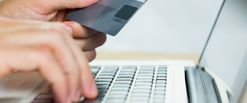 Person completing an online shopping purchase on laptop with credit card.