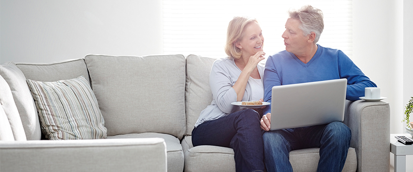 Couple have a conversation while using laptop together smiling.