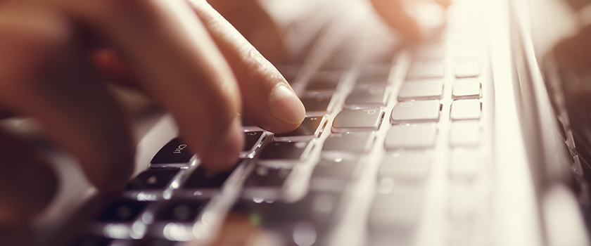 Person typing on laptop computer keyboard.
