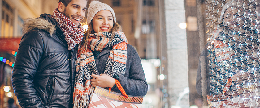 A couple smiling together while shopping at a store on Black Friday or Small Business Saturday.