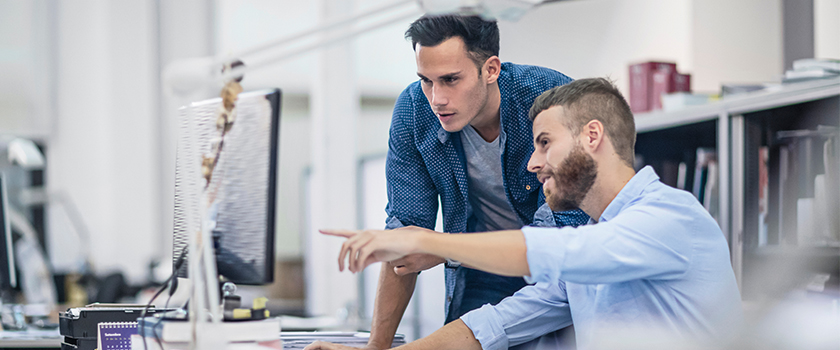 A man pointing at something on his computer to show his coworker what he found.