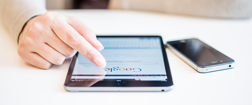 Person browsing on Google using a tablet.