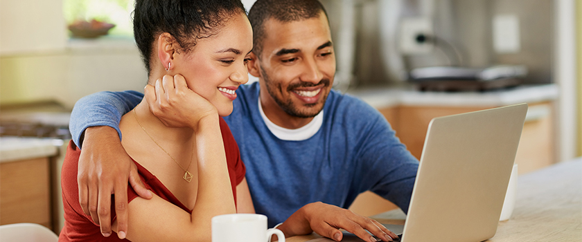 Man and woman looking at computer screen smiling.