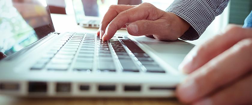 Man on computer typing on keyboard.