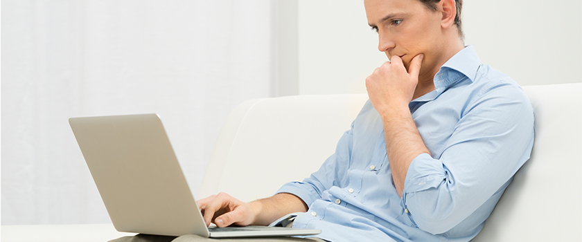 Man looking at laptop pondering how to improve his search engine rank.