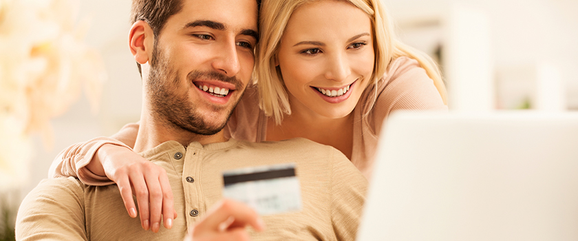 Couple smiling at laptop about to make a purchase with a credit card.