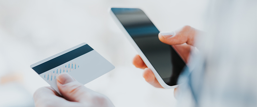 Person completing an online shopping transaction on their smartphone holding a credit card.