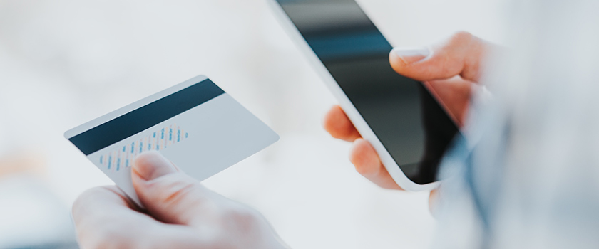 Person using credit card to make online purchase on their smartphone.