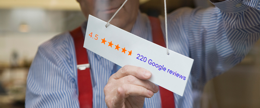Man putting sign on business door with a 4.5 star Google review summary