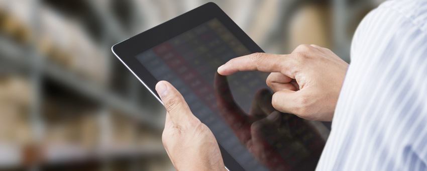 Man using tablet to check stock quantities in warehouse.